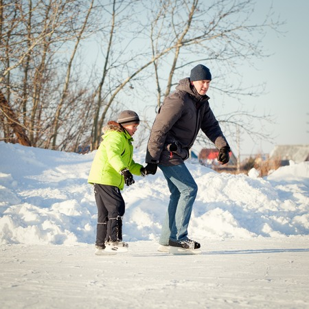Happy fun father and son learning to skate, winter, outdoor