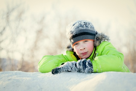 winterwear: Happy teen in winterwear smiling while playing in snowdrift outside