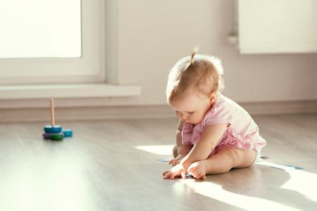 Kleine Mädchen spielen mit Pyramide auf dem Boden, Kindergarten, Frühreife