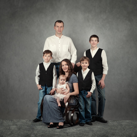 Portrait of big happy family on gray background in studio