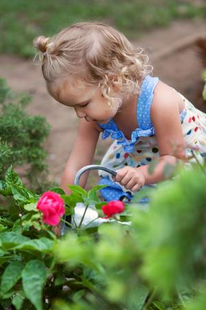 diligente: diligentes Niña que riega las flores lindo en el jardín de verano, al aire libre Foto de archivo