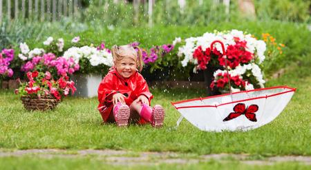 Happy fun pretty little girl in red raincoat with umbrella walking in park summer, ladybug costume, portrait, rain, outdoor