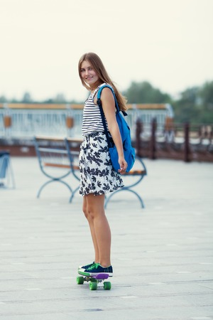 Young cute school girl rides skateboard on road, outdoor