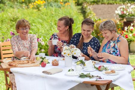 Elegant beautiful happy woman sitting at table, drinking tea and talking in summer garden, outdoor Standard-Bild