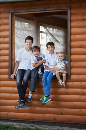 Portrait of happy handsome boys and little girl on background of wooden house, three brothers and small sister, outdoor photo
