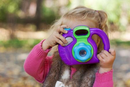 diligente: Retrato de la niña linda chica diligente y una cámara, el Parque de otoño., Al aire libre Foto de archivo