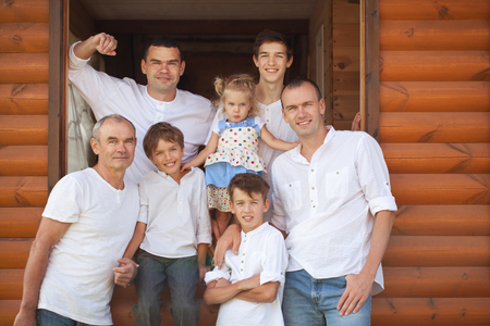Portrait of happy handsome men and little girl on background of wooden house, three generations, grandfather, father, son, grandson, outdoor photo