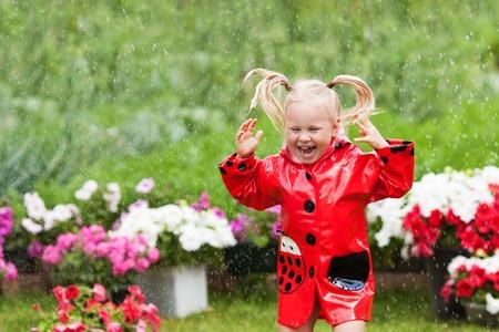 Happy Fun recht kleines Mädchen im roten Regenmantel mit Regenschirm im Park Sommer zu Fuß, Marienkäfer-Kostüm, Porträt, regen, im Freien