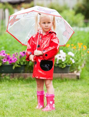 Ernst nachdenklich recht kleines Mädchen im roten Regenmantel mit Regenschirm Walking im Park Sommer, Marienkäfer-Kostüm, Porträt, regen, im Freien