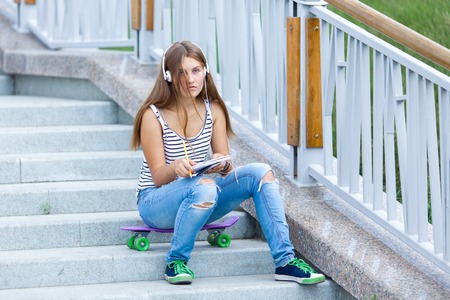 Portrait of Beautiful, happy young girl with smartphone sitting on stairs. She listens to music on headphones, outdoor, summer