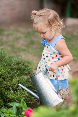 diligente: diligentes Niña que riega las flores lindo en el jardín de verano, al aire libre