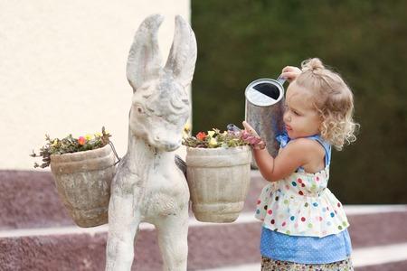 fleißig niedliche kleine Mädchen Bewässerung der Blumen im Sommer Garten, im Freien