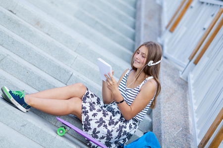 Beautiful, happy young girl with smartphone sitting on stairs. She listens to music on headphones, outdoor, summer