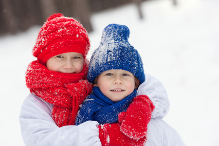 portrait of happy brother and sister in costumes snowman walking in winter forest, outdoor