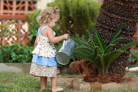 diligent cute little girl watering flowers in summer garden, outdoor