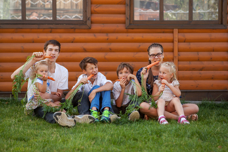 Portrait of happy handsome boys and girl on background of wooden house, three brothers and sister eating carrots, outdoor photo