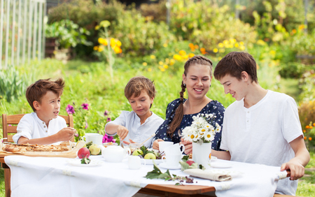 Happy nice brother and sister drinking tea in summer green garden. Portrait of group of people. outdoor photo