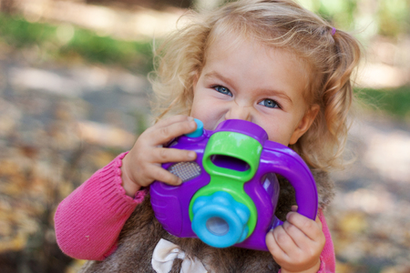 diligente: Portrait of diligent cute little girl girl and camera, autumn park., outdoor