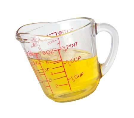 Cooking Oil in Measuring Cup isolated on white Standard-Bild