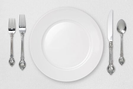 White plate setting on tablecloth Standard-Bild