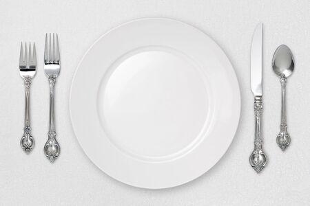 White plate setting on tablecloth Standard-Bild