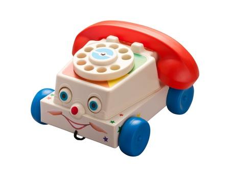 Antieke stuk speelgoed telefoon op wit wordt geïsoleerd