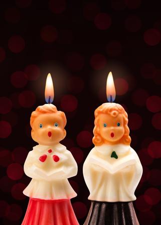 chorus: Choir Boy and Girl Candles isolated on a dark background.