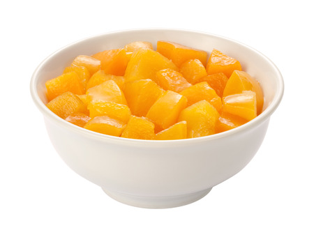 Diced Peaches in a white bowl, isolated on white with a clipping path.