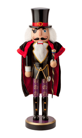 nobleman: Vintage wooden aristocrat nutcracker with a top hat and cape. This nobleman has white hair and a beard, and sports a black eye patch. The cape is black with red trim and the hat is black with a red hat band and gold buckle. He carries a black cane and a g