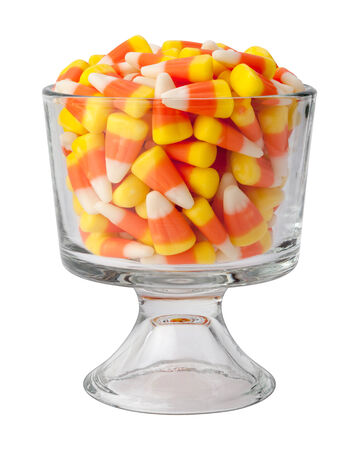 str: Candy corn in a dessert glass. This candy is a Halloween tradition and is given out as a treat to kids as they go door to door. The three colors of the candy are orange, yellow, and white, and mimic the appearance of corn kernels. The point of view is str