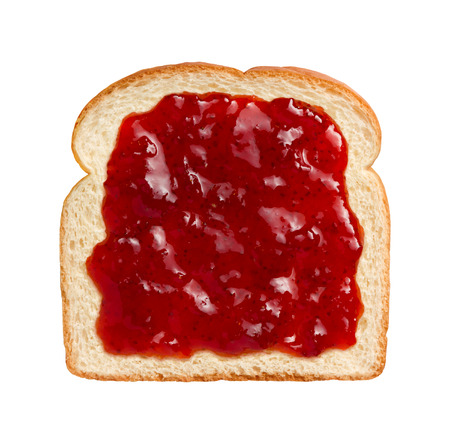 Aerial view of bright red strawberry preserves, spread over a slice of white bread. This can be eaten as shown or combined with another piece of bread and other ingredients to make a sandwich. The subject is isolated on a white background and was shot wit