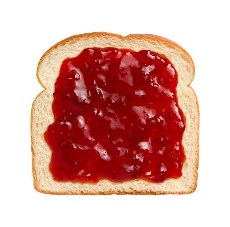 mermelada: Vista aérea de brillantes mermelada de frutillas rojas, repartidos en una rebanada de pan blanco. Esto se puede comer como se muestra o combinado con otro pedazo de pan y otros ingredientes para hacer un sándwich. El sujeto está aislado en un fondo blanco y le dispararon ingenio