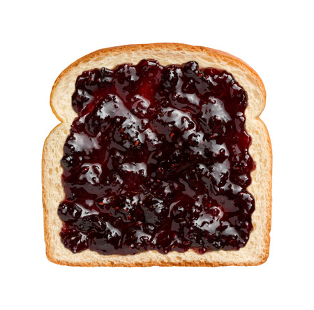 Aerial view of mixed berries preserves, spread over a slice of white bread. This jam contains strawberries, blackberries, raspberries, blueberries, and can be eaten as shown or combined with another piece of bread and other ingredients to make a sandwich. Stock Photo