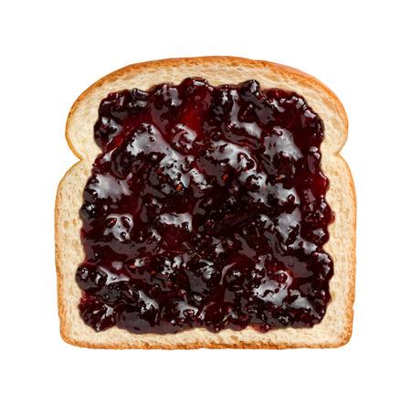 Veduta aerea di frutti di bosco misti conserve, si sviluppa su una fetta di pane bianco. Questa confettura contiene fragole, more, lamponi, mirtilli, e può essere consumato come indicato o in combinazione con un altro pezzo di pane e altri ingredienti per fare un panino. Archivio Fotografico - 33647481