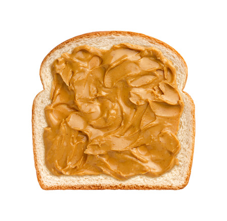 Aerial view of swirling peanut butter on a  slice of white bread.