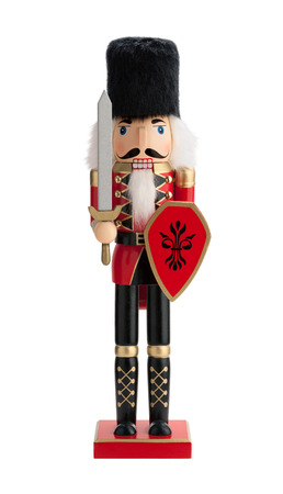 Antique Nutcracker Guard with a sword and red shield. He has white hair and beard. He sports a black bearskin fur hat, with a red coat and black boots. The point of view is straight on, and is isolated on a white background.