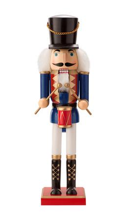 tambor: Antique Cascanueces del batería con un tambor rojo. Él tiene el pelo blanco y barba. Él se divierte un sombrero negro, con un abrigo azul y botas negras. El punto de vista es recto, y está aislado en un fondo blanco.