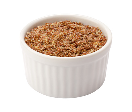 flaxseed: Flax Seed Meal in a white Ramekin. The point of view is straight on. The subject is isolated on white and includes a clipping path. Stock Photo