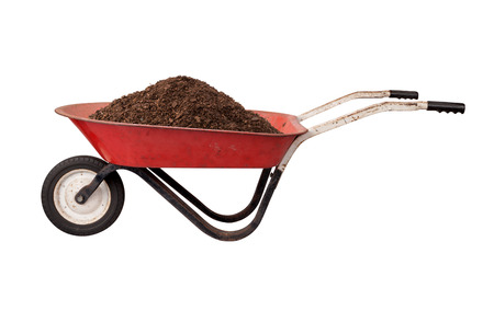 Rusty Red Wheelbarrow loaded with Soil, isolated on white.