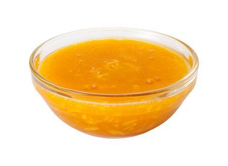 mango: Mango Coconut Marinadein w szklanej misce. Ten sos jest idealny do aromatyzowania ryby. Ryby i inne produkty są moczone przed gotowaniem, aby ich smak lub zmiękczyć. Obraz jest wyciąć, odizolowane na białym tle, z wycinek trasy. Zdjęcie Seryjne