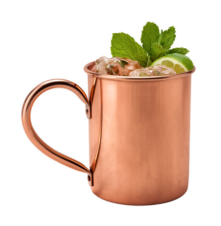 cocktail drinks: Moscow Mule in a Copper Mug. This is a Vodka drink served with mint, and a garnished with a wedge of lime, The image is a cut out, isolated on a white background, and includes a clipping path. Stock Photo