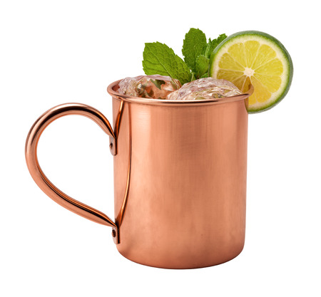 mug: Moscow Mule in a Copper Mug. This is a Vodka drink served with mint, and a garnished with a wedge of lime, The image is a cut out, isolated on a white background, and includes a clipping path. Stock Photo