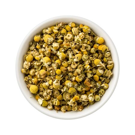 dried spice: Loose Leaf Chamomile in a Ceramic Bowl. These dried spice leaves and flowers can be used to make herbal tea. The image is a cut out, isolated on a white background, with a clipping path.