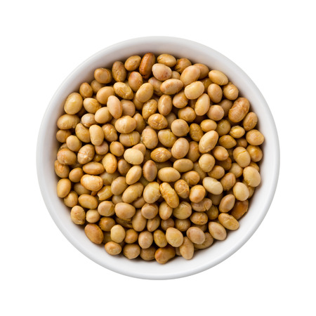 Overhead View of Roasted Soy Nuts in a Ceramic Bowl. Soy nuts are made from soybeans soaked in water, drained, and then baked or roasted. They can be used in place of nuts and are high in protein and dietary fiber. The image is a cut out, isolated on a wh Stock Photo