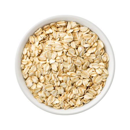 Overhead View of Organic Rolled Oats in a ceramic bowl. Rich in fiber and nutrition. The image is a cut out, isolated on a white background, with a clipping path. Foto de archivo