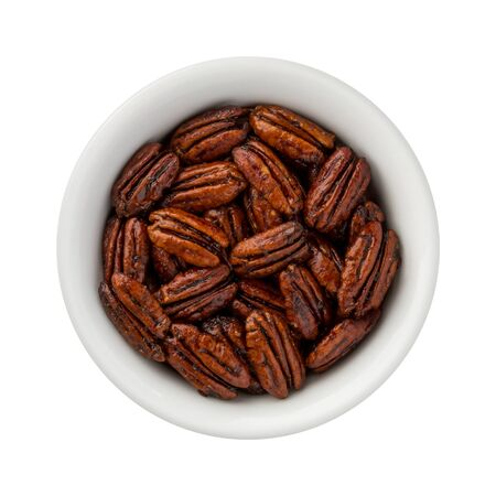 Caramelized Pecans in a ceramic bowl. The image is a cut out, isolated on a white background, with a clipping path. Stock Photo