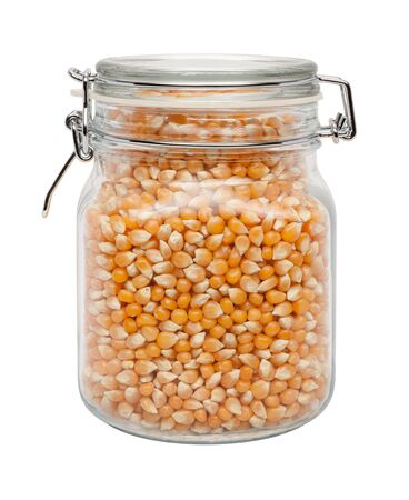 kitchenware: Uncooked Popcorn in a Glass Canister with a Metal Clamp. The image is a cut out, isolated on a white background, with a clipping path.