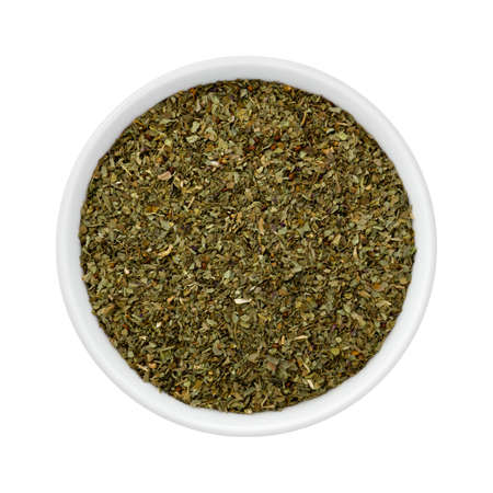 Dried Basil Flakes in a Ceramic Bowl. The image is a cut out, isolated on a white background, with a clipping path.