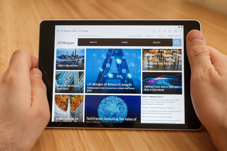 SAN FRANCISCO, US - 1 April 2019: Close up to hands holding tablet using internet and looking through J P Morgan web site, in San Francisco, California, USA. An illustrative editorial image