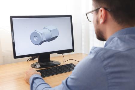 Ingénieur, constructeur, concepteur de lunettes travaillant sur un ordinateur personnel. Il crée et conçoit un nouveau modèle 3D de composant mécanique dans un programme de CAO. Travail autonome.
